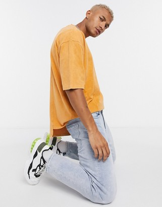 ASOS DESIGN oversized T-shirt with half sleeve in heavyweight yellow acid wash with stepped hem