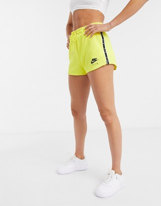 Nike logo tape shorts in yellow