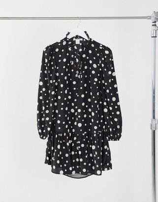 Glamorous mini smock dress with tie neck and peplum hem in spot