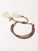 White Stuff Hessian tassel bracelet
