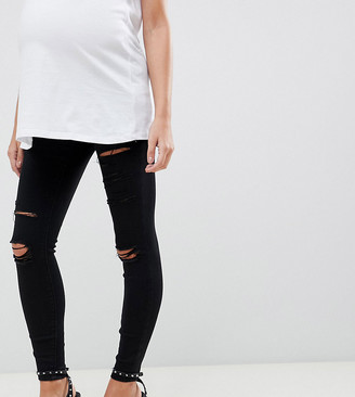 Asos DESIGN Maternity Ridley high waisted skinny jeans in black with shredded rips and under the bump waistband