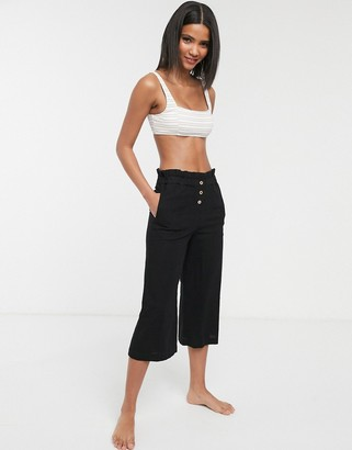 Accessorize beach pants with button detail in black