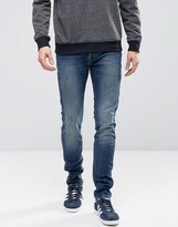 Jack and Jones Intelligence Slim Fit Jeans In Mid Blue Wash With Rip Repair Detail