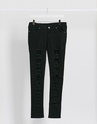 Criminal Damage skinny jeans with extreme rips and lace in black