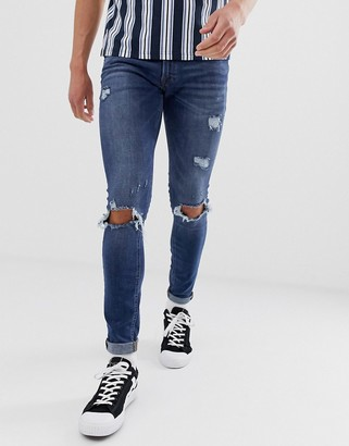 Jack and Jones Intelligence spray on skinny jeans with rip detail in mid blue