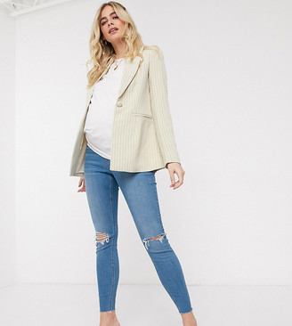 ASOS DESIGN Maternity high rise ridley 'skinny' jeans in lightwash blue with knee rips and raw hem with under bump