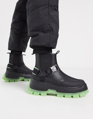 Asos DESIGN chelsea boots in black with strapping details and chunky cleated sole with neon pop