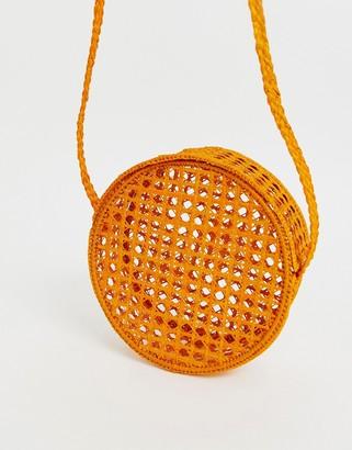 Kaanas net woven raffia round cross body bag in orange