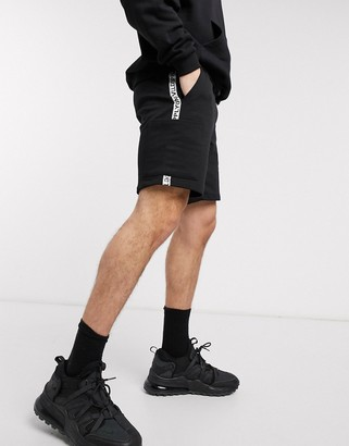 Asos DESIGN relaxed shorts in black with side pockets and unrvlld/supply brand taping detail