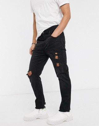 ASOS DESIGN tapered carrot fit jeans in washed black with heavy rips