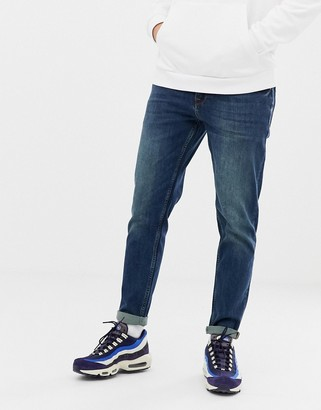 Asos DESIGN tapered jeans in dirty blue wash
