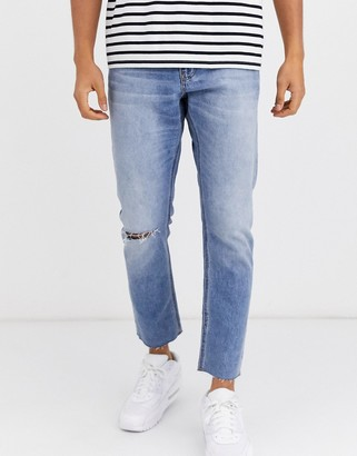 ASOS DESIGN cropped slim jeans in light wash with raw hem and knee rip
