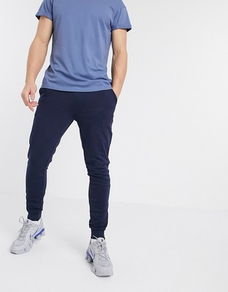 ASOS DESIGN organic super skinny sweatpants in navy with silver zip cuffs