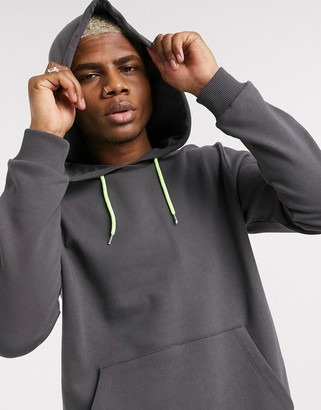 ASOS DESIGN hoodie in washed black with neon yellow drawcords