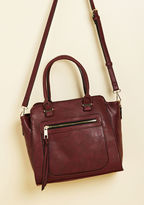 10717BML This burgundy purse is the most posh way to tote your things! Made with faux leather, gold hardware, and an optional shoulder strap, this structured satchel is primed for your ever-stylish escapades.