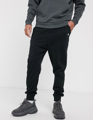 ASOS DESIGN lightweight drop crotch joggers in black with triangle
