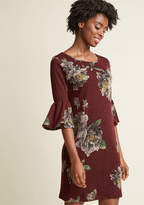 D12399 This burgundy dress takes you from romantic brunch to craft cocktails seamlessly and in style! Ruffled 3/4-length sleeves are a playful touch for toasting mimosas, while the fitted knit silhouette of this floral frock offers an allure that's appropriate f