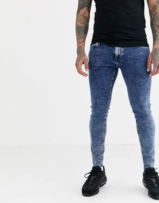 Jack and Jones Intelligence spray on skinny fit jeans with raw hem in blue acid wash