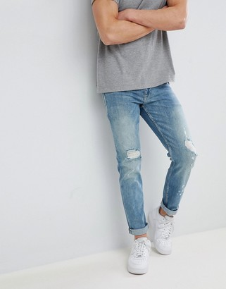 ASOS DESIGN stretch slim jeans in mid wash blue with rips