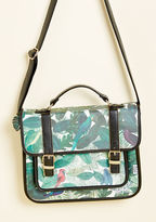 eye satchel Before you even board the plane, you'll feel whisked away to lush locales by having this faux-leather satchel from Disaster Designs handy! Black and gold accents frame the green jungle print of this 'tropi-cool' bag, while its pink lining reflects the sam
