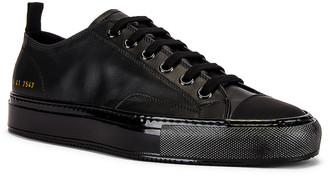Common Projects Tournament Low Leather Shiny Sneaker in Black & Black | FWRD
