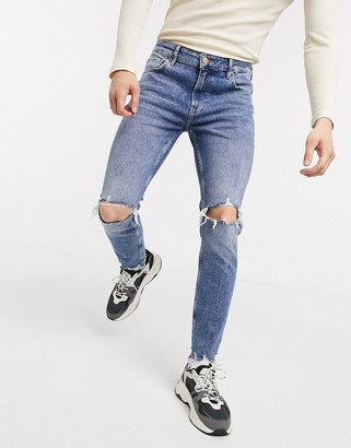 Bershka skinny jeans with knee rips and raw hem in mid wash blue