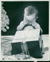 PickYourImage Vintage photo of Child rubbing his eyes while gift boxes in front of him.