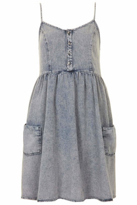 Babydoll Denim dress. cut with a high waist and smocked back. features two front pockets and button front detail. team with flats
